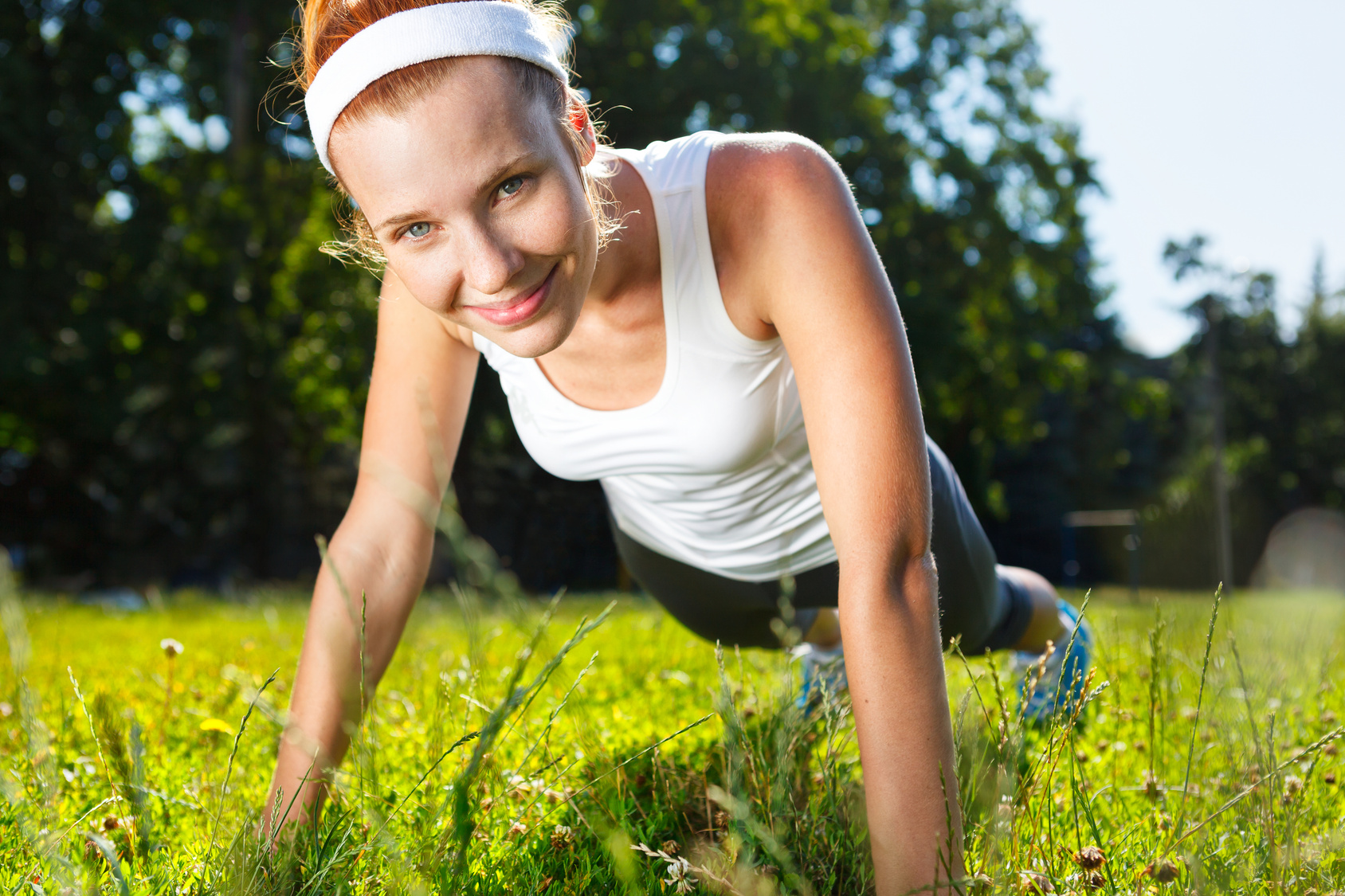 Young woman doing push ups on green grass